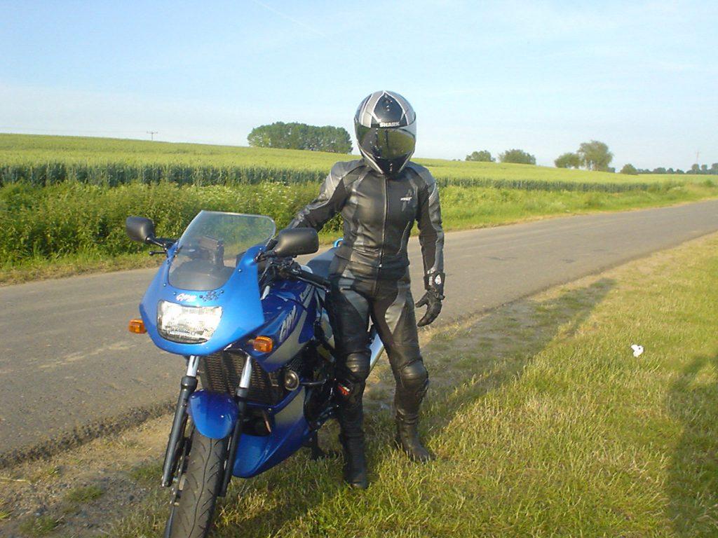 Volle Schutzausrüstung mit Helm, Lederkombi Stiefel und Handschuhe.