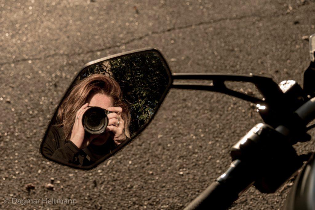 Dagi fotografiert sich im Rückspiegel und reflektiert über das Leben.