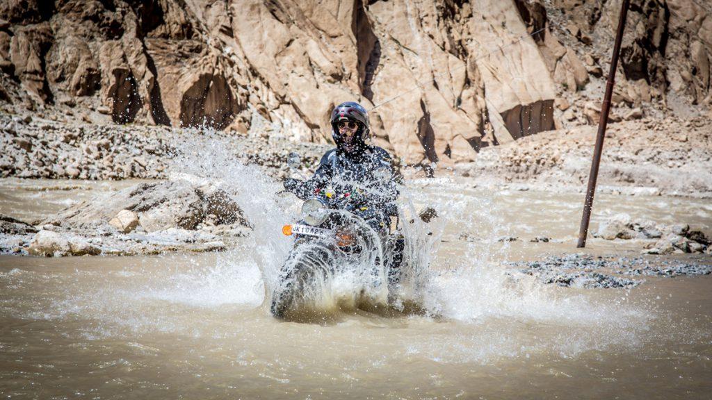 Im Motorradurlaub durch einen Fluss im Himalaya.