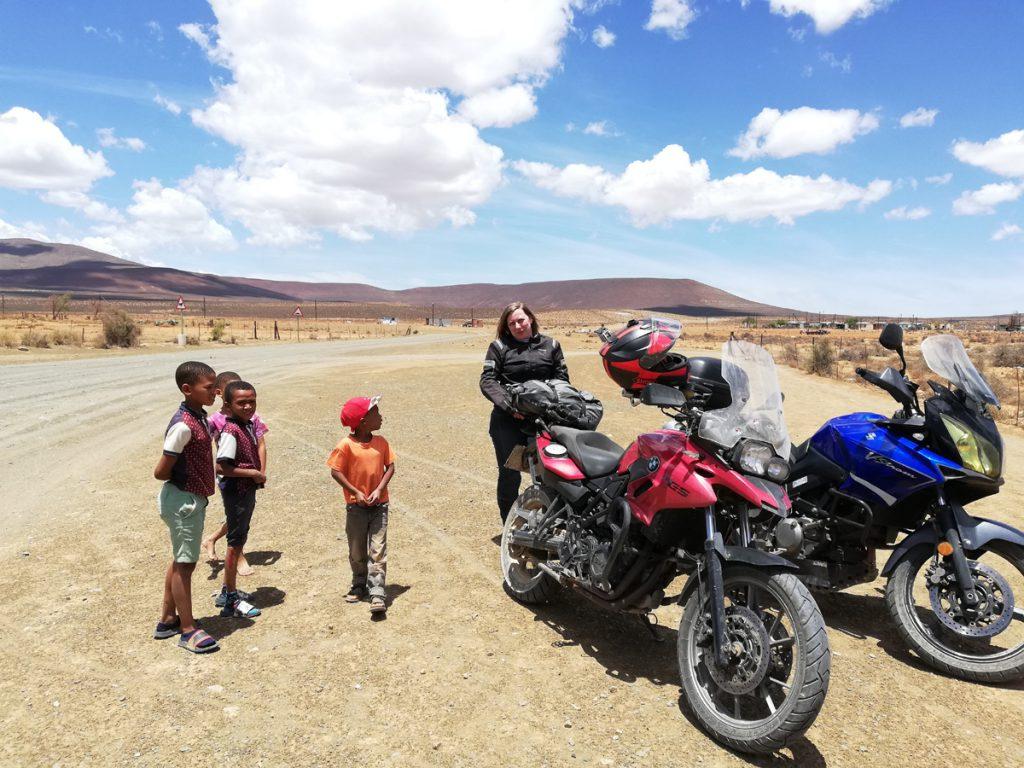 Motorrad am Straßenrand mit neugierigen Kindern. Kommunkation mit Lächeln, Händen und Füßen.
