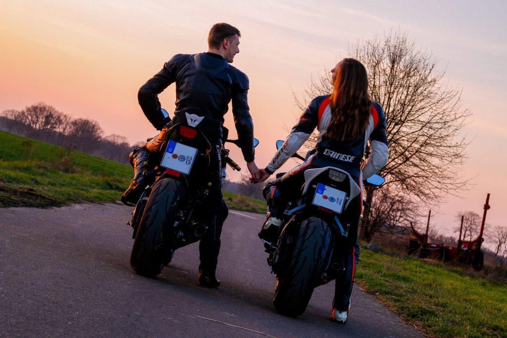 Geena She is a Rider mit Motorrad und Freund im Sonnenuntergang